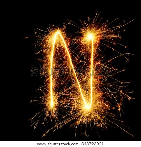 English alphabet from golden sparkler on black background - stock photo