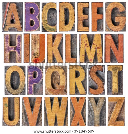 English alphabet in wood type - 26 isolated letters in letterpress printing blocks with a lot of character due to scratches and ink stain - stock photo