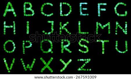 English alphabet, letters of Christmas lights, green bokeh. - stock photo