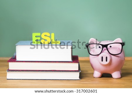 English as a Foreign Language ESL theme with pink piggy bank with chalkboard in the background as concept image of the costs of education - stock photo