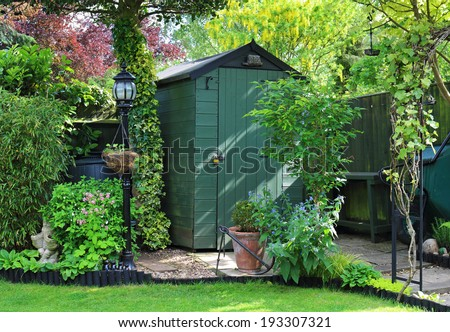 English back garden with shed amongst the plants - stock photo
