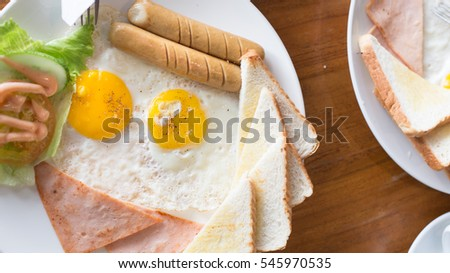 English breakfast background. Closeup fried eggs, hot beans salad cream and delicious toast serve directly in every morning.