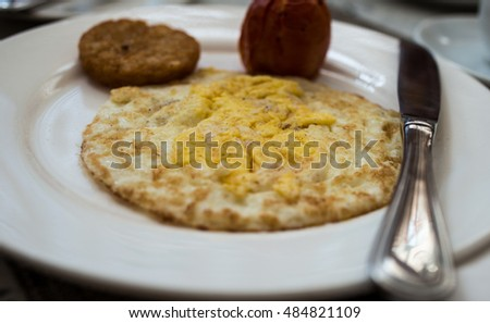 English Breakfast, eggs, grilled tomato and pan fried potatoes in white dish and cup of coffee