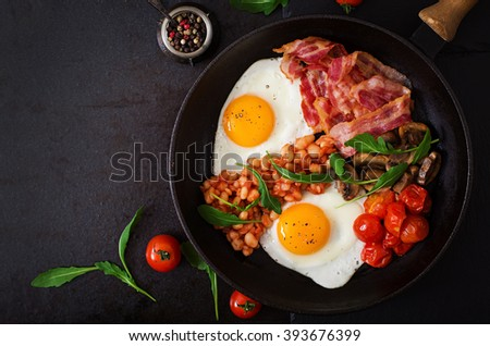 English breakfast - fried egg, beans, tomatoes, mushrooms, bacon and toast. Top view - stock photo