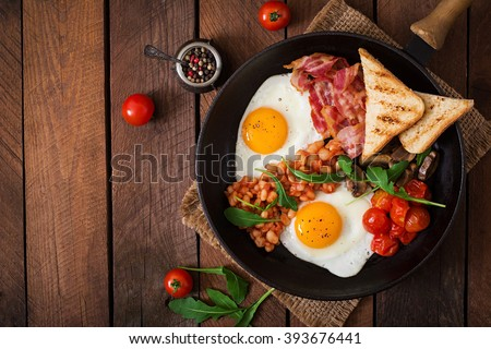 English breakfast - fried egg, beans, tomatoes, mushrooms, bacon and toast. Top view