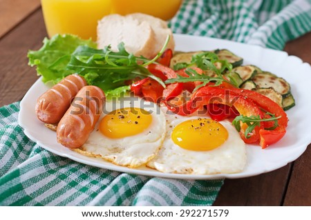 English breakfast - fried eggs, sausages, zucchini and sweet peppers - stock photo