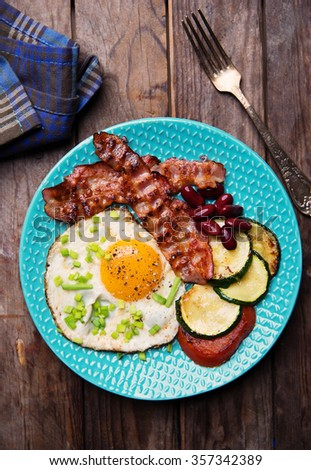 English breakfast - fried eggs, sausages, zucchini and tomatoes - stock photo