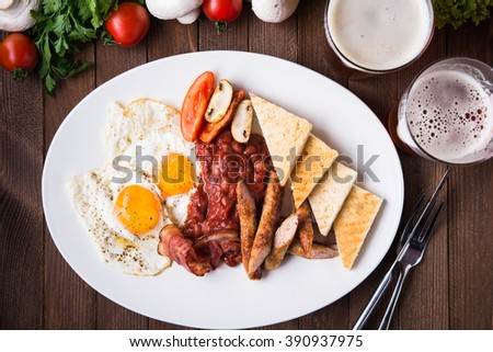 English breakfast (poached eggs, beans, roasted bacon, sausages and vegetables) on dark wood background top view. - stock photo