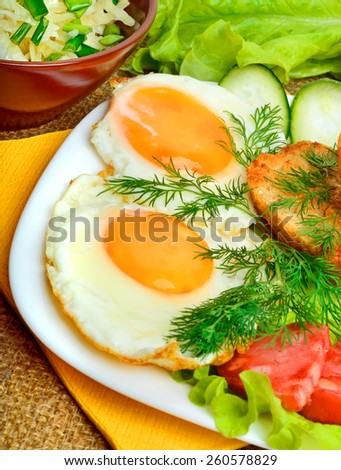 English breakfast, scrambled eggs with toasts, bacon, ham and vegetables. Salad with cabbage, cucumber. - stock photo