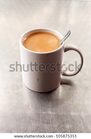 English breakfast tea that is in a white colored mug.  This images was taken in a traditional British working men's cafe on an outside silver colored table - stock photo