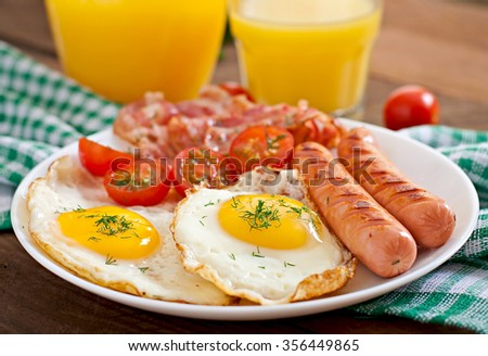 English breakfast - toast, egg, bacon and vegetables in a rustic style on wooden background.