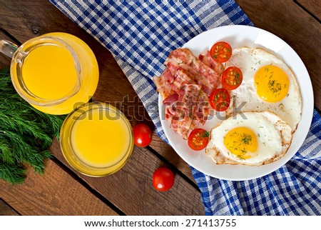 English breakfast - toast, egg, bacon and vegetables in a rustic style on wooden background. Top view. - stock photo