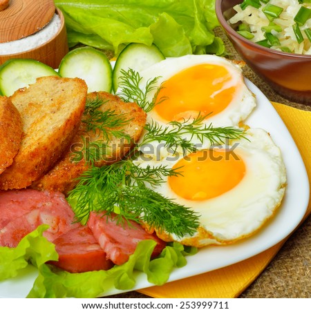 English breakfast - toast, egg, bacon and vegetables. Salad, cabbage, cucumber.