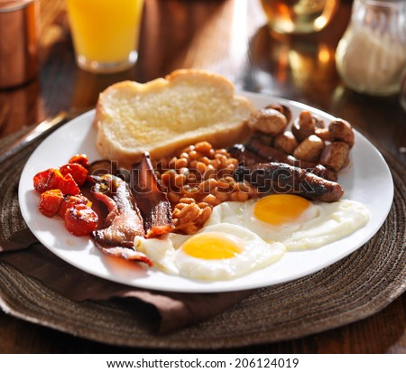 english breakfast with eggs, tomatoes, mushrooms, bacon, beans, and sausage - stock photo