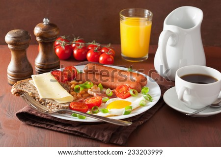english breakfast with fried egg sausages bacon tomatoes beans - stock photo