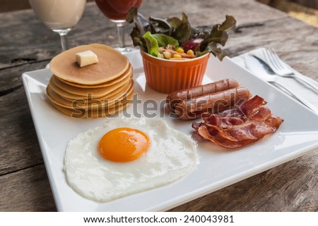 English breakfast with fried eggs, bacon, sausages and salad - stock photo