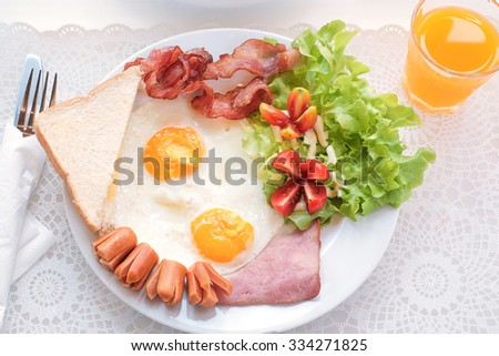 English breakfast with fried eggs, bacon, sausages, toasts and fresh salad - stock photo