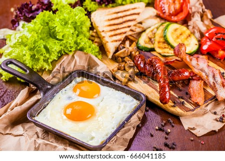 English breakfast with fried eggs, sausages, bacon, vegetables, bread and spices