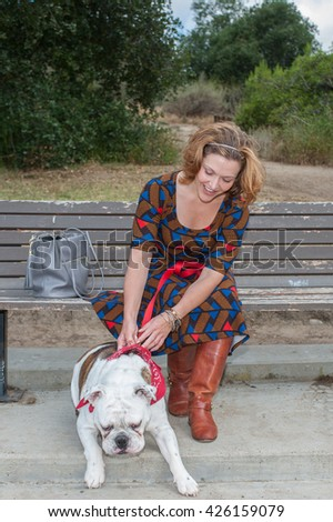 English Bulldog trying to pull attractive women off park bench.