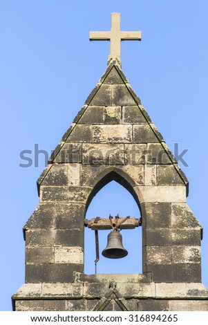 English Church Bell Tower with exposed bell and cross against a blue sky - stock photo