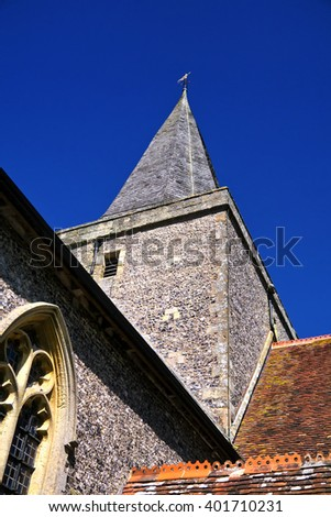 English church tower and spire; detail of historic old church against blue sky  - stock photo