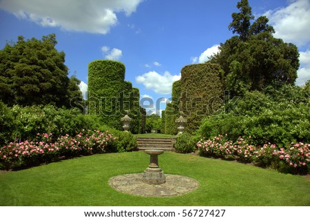 English country garden with sundial and topiary shrubs - stock photo