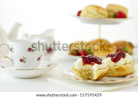 English Cream tea scene with scones, Devonshire style, with a bite taken out. Part of a series showing the preparation of scones.