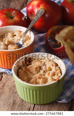 English crumble with apples close-up in the pot. vertical rustic style