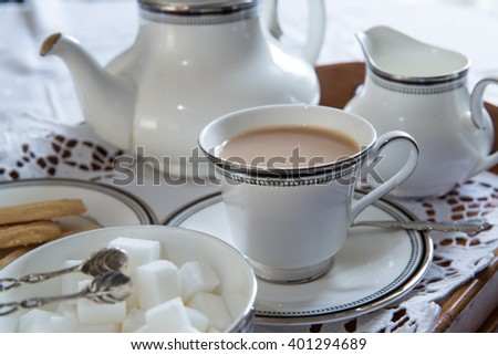 English cup of tea with teapot, sugar and biscuits - stock photo
