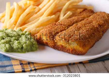 English food: fried fish fillets and chips and pea puree close-up on a plate. horizontal - stock photo