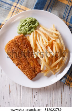 English food: fried fish in batter with chips and pea puree close-up on a plate. vertical top view - stock photo