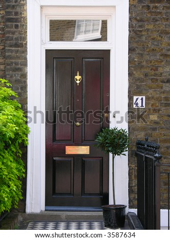 English front door. Surrounded by flowers. - stock photo