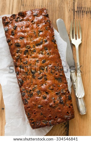 English fruit cake on white paper on brown wooden background with fork and knife