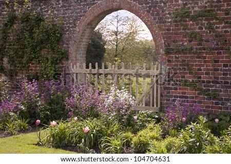 English Garden Border & Old Brick Arch - stock photo