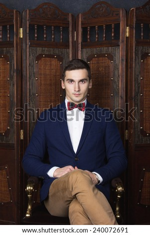 English gentleman beauty concept. Portrait of young and handsome man in blue jacket, Scottish bow tie and white shirt posing over vintage screen. Close up. Studio shot - stock photo