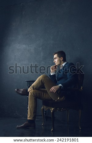 English gentleman beauty concept. Portrait of young and handsome man in blue jacket, Scottish bow-tie and white shirt posing over blue background. Close up. Studio shot - stock photo