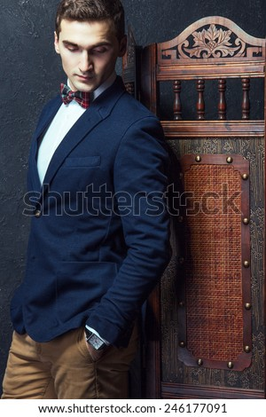 English gentleman beauty concept. Portrait of young and handsome man in blue jacket, Scottish bow-tie and white shirt posing over vintage screen. Close up. Studio shot - stock photo