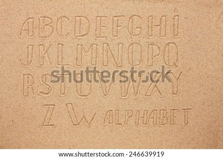 English, German, Portuguese alphabet  written on the sand, as background - stock photo