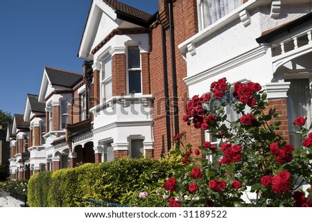 English Homes with roses. Row of Typical English Terraced Houses with red roses in the foreground at London. - stock photo