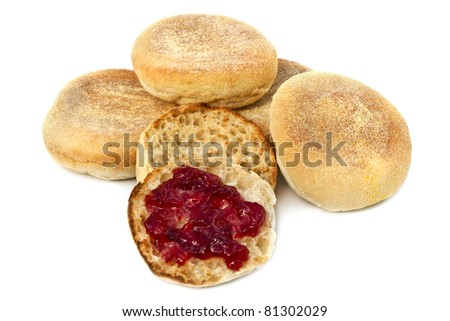 English muffins over white background.  One is toasted, with strawberry jam. - stock photo