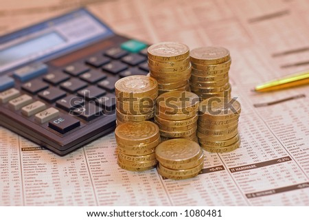 English One and two pound coins on financial page and calculator background. - stock photo