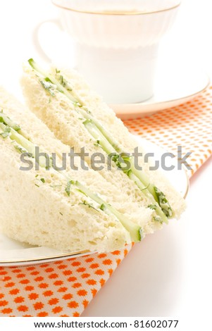 English sandwiches. Stuffing a cucumber, dill and butter. The shape is triangular. In the background is visible with a cup of tea.