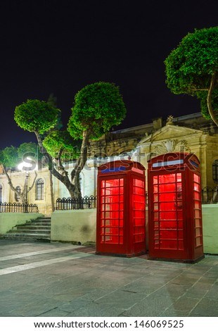 English telephone box on Malta a summer night in the light of lanterns with trees