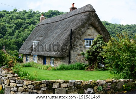 English thatched cottage in a picturesque Yorkshire village - stock photo