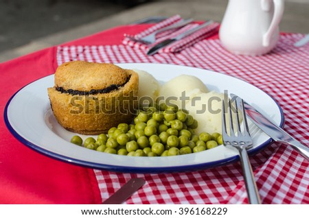 English traditional pie with mashed potatoes and garden green peas with gravy on the red table - stock photo