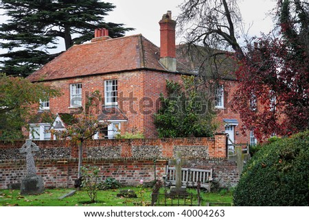 English Village Manor Farmhouse viewed from the Churchyard over a Brick and Flint Wall - stock photo