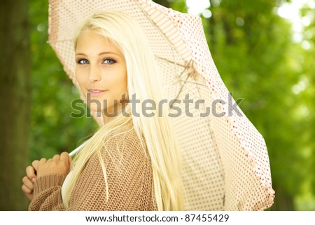 Enigmatic Beauty With Umbrella, beautiful blonde female model posing in park under polka dot umbrella. - stock photo