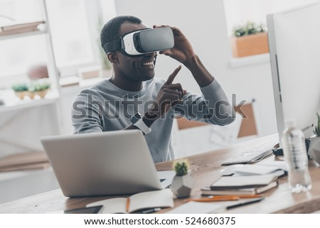 Enjoing innovation technologies. Good looking young African man in virtual reality headset pointing in the air while sitting at the desk in creative office