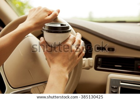 Enjoy a cup of coffee to go to keep you concentrated on the way to work or holidays. Driving assistance. - stock photo