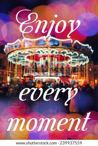 ENJOY EVERY MOMENT. Inspirational Typographic Quote. Merry-Go-Round illuminated at night with colorful bokeh - stock photo